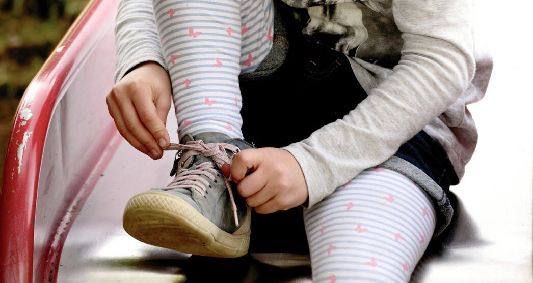 Little girl tying her shoes on a red slide