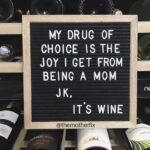 """Decorative sign propped up on wine rack saying """"My drug of choice is the joy I get from being a mom. Jk. It's wine."""""""