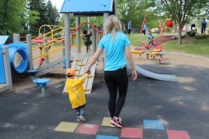 Blonde woman with blue shirt holding hands of child in yellow coat walking away from the camera towards a playground