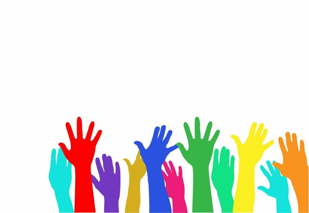 Different multicoloured hands raised to volunteer.