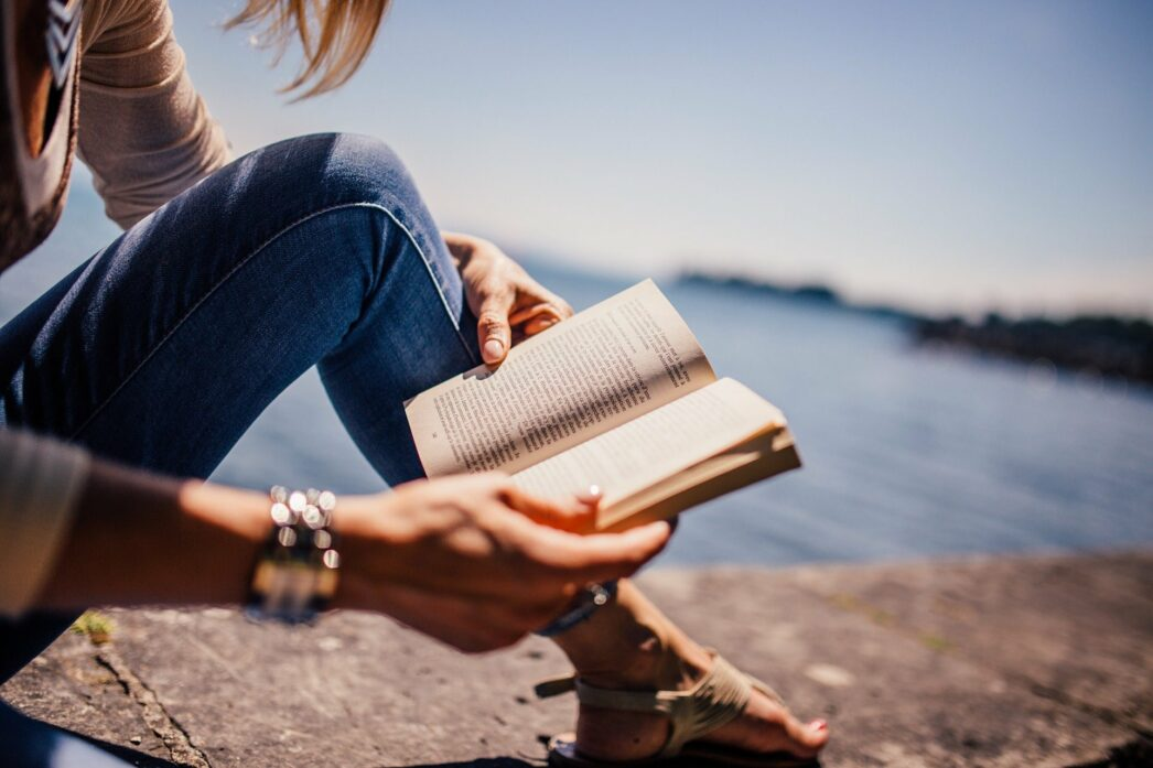 Woman sitting on the ground reading a book in front of a lake.