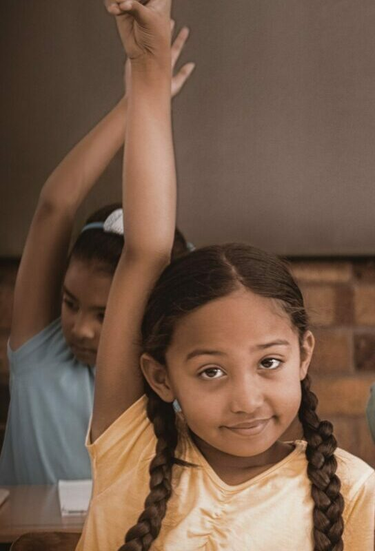 Girl in yellow shirt with pigtail braids raising her hand to ask a question in class