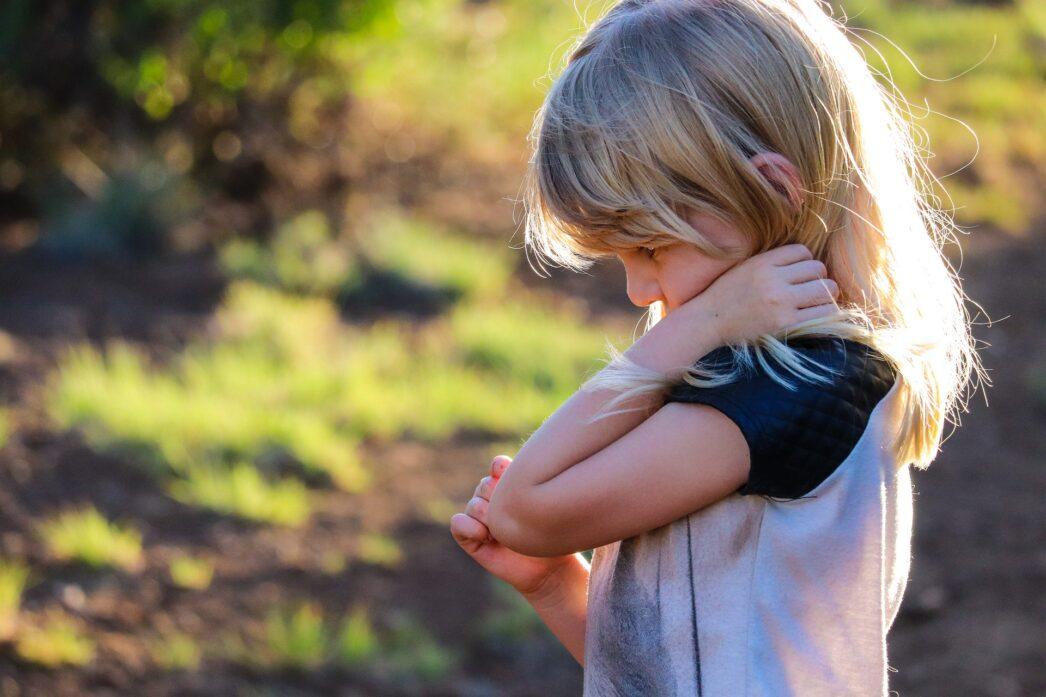 Blonde child holding her hurt elbow